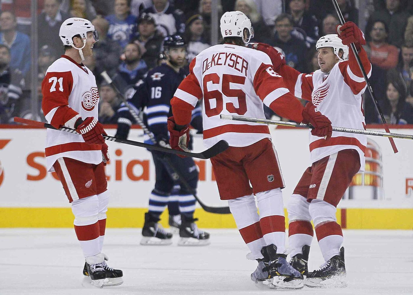 Detroit Red Wings forwards Daniel Cleary (71), Danny DeKeyser (65) and Stephen Weiss celebrate DeKeyser's second-period goal. (JOHN WOODS / THE CANADIAN PRESS)