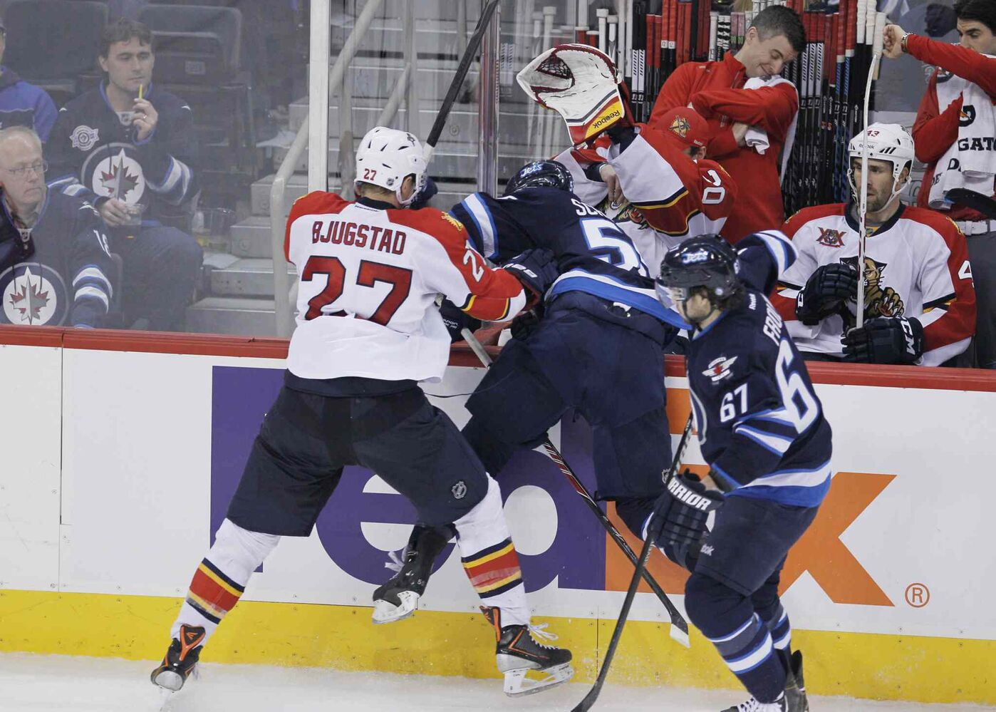 Winnipeg Jets' Mark Scheifele (55) gets dumped into the Florida bench by Florida Panthers' Nick Bjugstad (27) as Jets' Michael Frolik (67) skates by during third period. (John Woods / The Canadian Press)