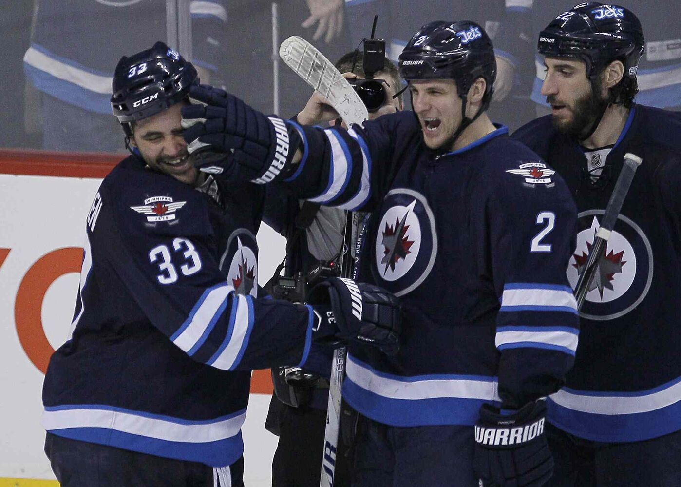 Winnipeg Jets' Dustin Byfuglien (33) and Adam Pardy (2) celebrate Byfuglien's winning overtime goal. The Jets beat the Toronto Maple Leafs 5-4 in Winnipeg on Saturday.