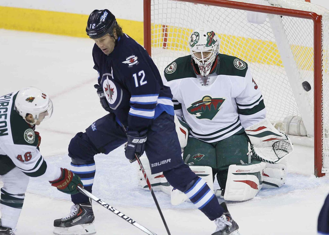 Wild goaltender Ilya Bryzgalov stops a deflection by Jets forward Olli Jokinen as the Wild's Jared Spurgeon defends during the first period. (JOHN WOODS / WINNIPEG FREE PRESS)