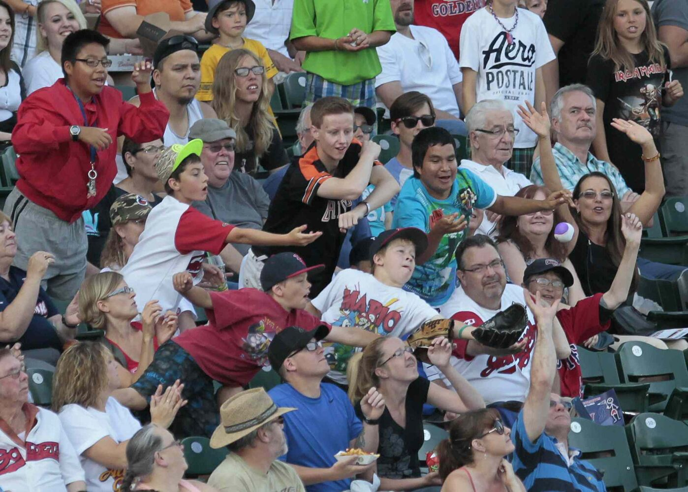 Fans lunge for a flying ball at the 2014 American Association All-Star game in Winnipeg Tuesday. (John Woods / Winnipeg Free Press)