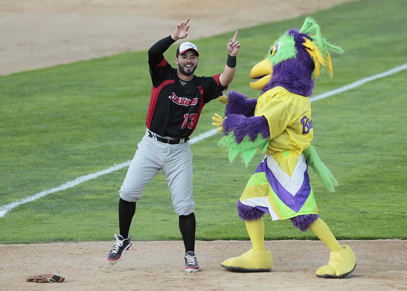 Grand Prairie Air Hogs Adel Nieves jokes around with a mascot during Tuesday's All-Star game. (John Woods / Winnipeg Free Press)