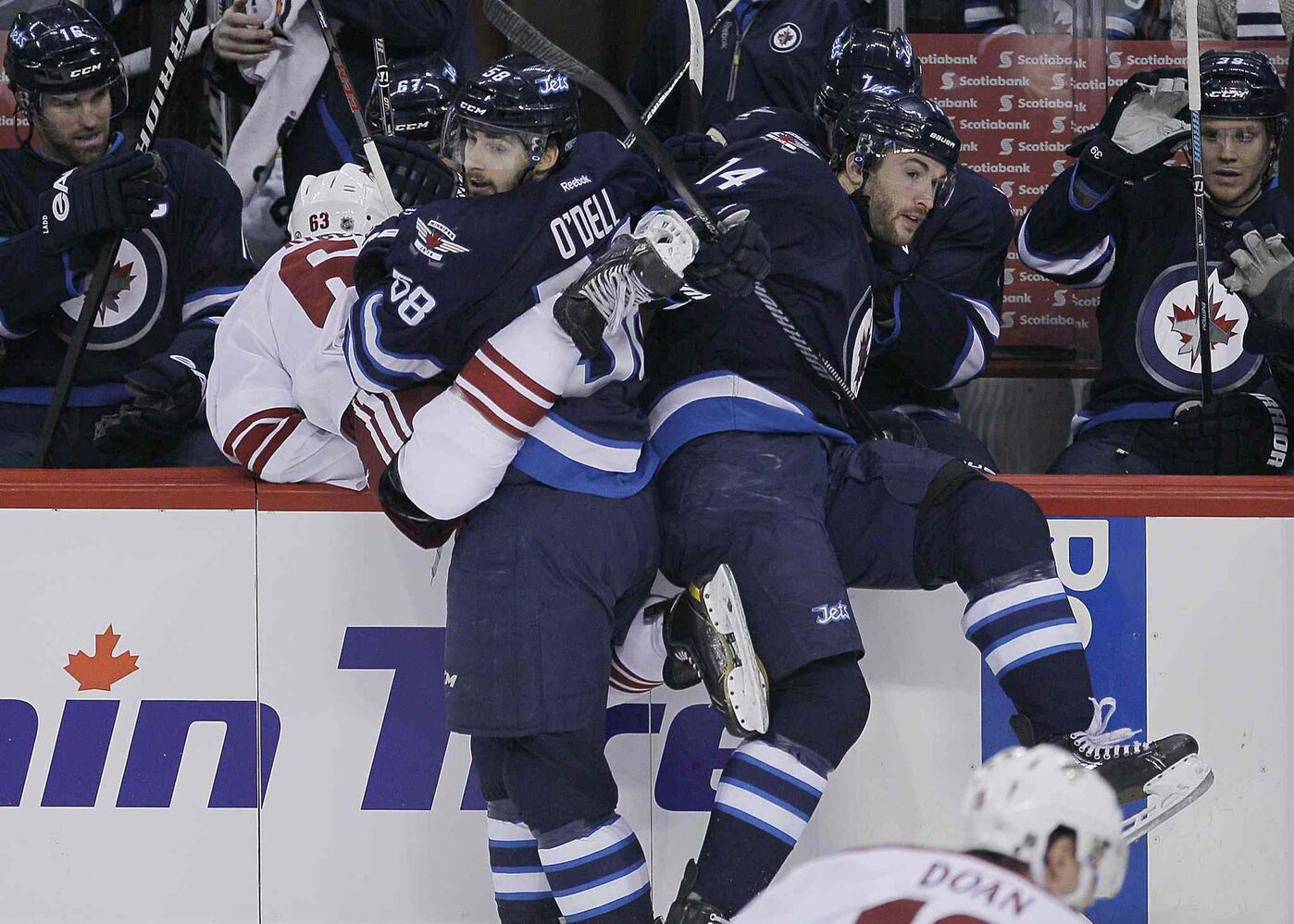 Winnipeg Jets' Eric O'Dell (58) and Anthony Peluso (14) check Phoenix Coyotes' Mike Ribeiro over the boards.