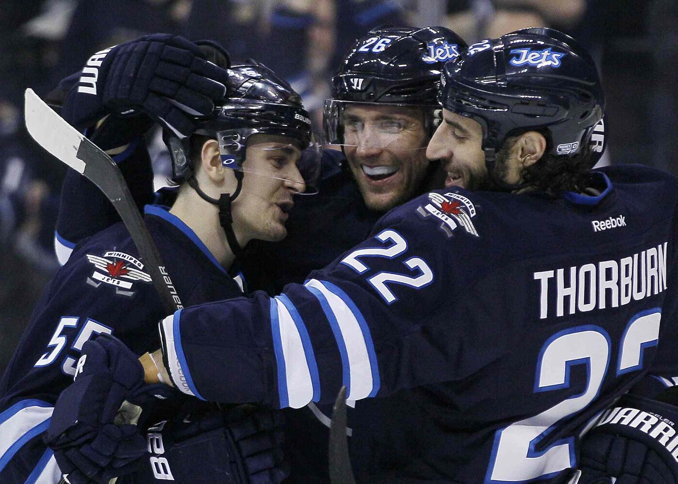 Jets Mark Scheifele (left), Blake Wheeler and Chris Thorburn (right) celebrate Wheeler's goal.