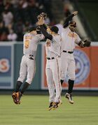 Baltimore Orioles left fielder David Lough, from left, right fielder Nick Markakis and center fielder Adam Jones celebrate their team's 4-2 win against the Los Angeles Angels in a baseball game on Monday, July 21, 2014, in Anaheim, Calif. (AP Photo/Jae C. Hong)