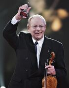 Buddy MacMaster raises his Dr. Helen Creighton Lifetime Achievement Award at the East Coast Music Award in Charlottetown in this Feb 27, 2006 file photo. Buddy MacMaster has died at age 89. THE CANADIAN PRESS/Jacques Boissinot
