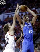Oklahoma City Thunder center Steve Adams, from New Zealand, right, shoots against Portland Trail Blazers center Robin Lopez during the first half of an NBA basketball game in Portland, Ore., Wednesday, Oct. 29, 2014.(AP Photo/Don Ryan)