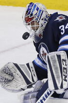 Winnipeg Jets goaltender Michael Hutchinson (34) keeps a close eye on the puck as he saves the Columbus Blue Jackets' shot off his mask.