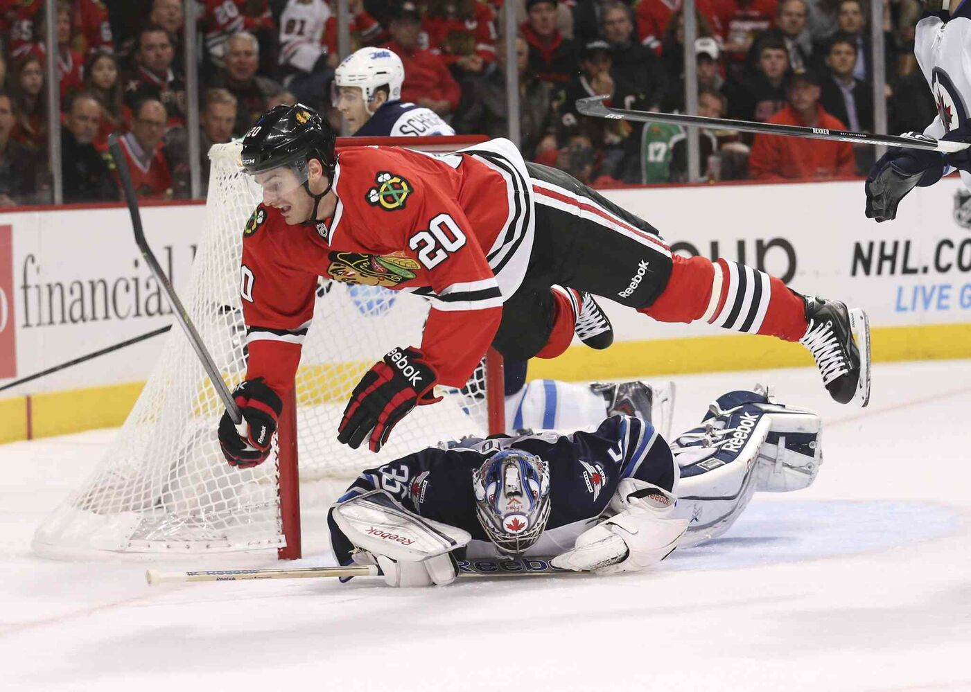 Brandon Saad (20) of the Chicago Blackhawks dives over goalie Al Montoya of the Winnipeg Jets while chasing a puck during the first period. (Nuccio DiNuzzo / Chicago Tribune / MCT)