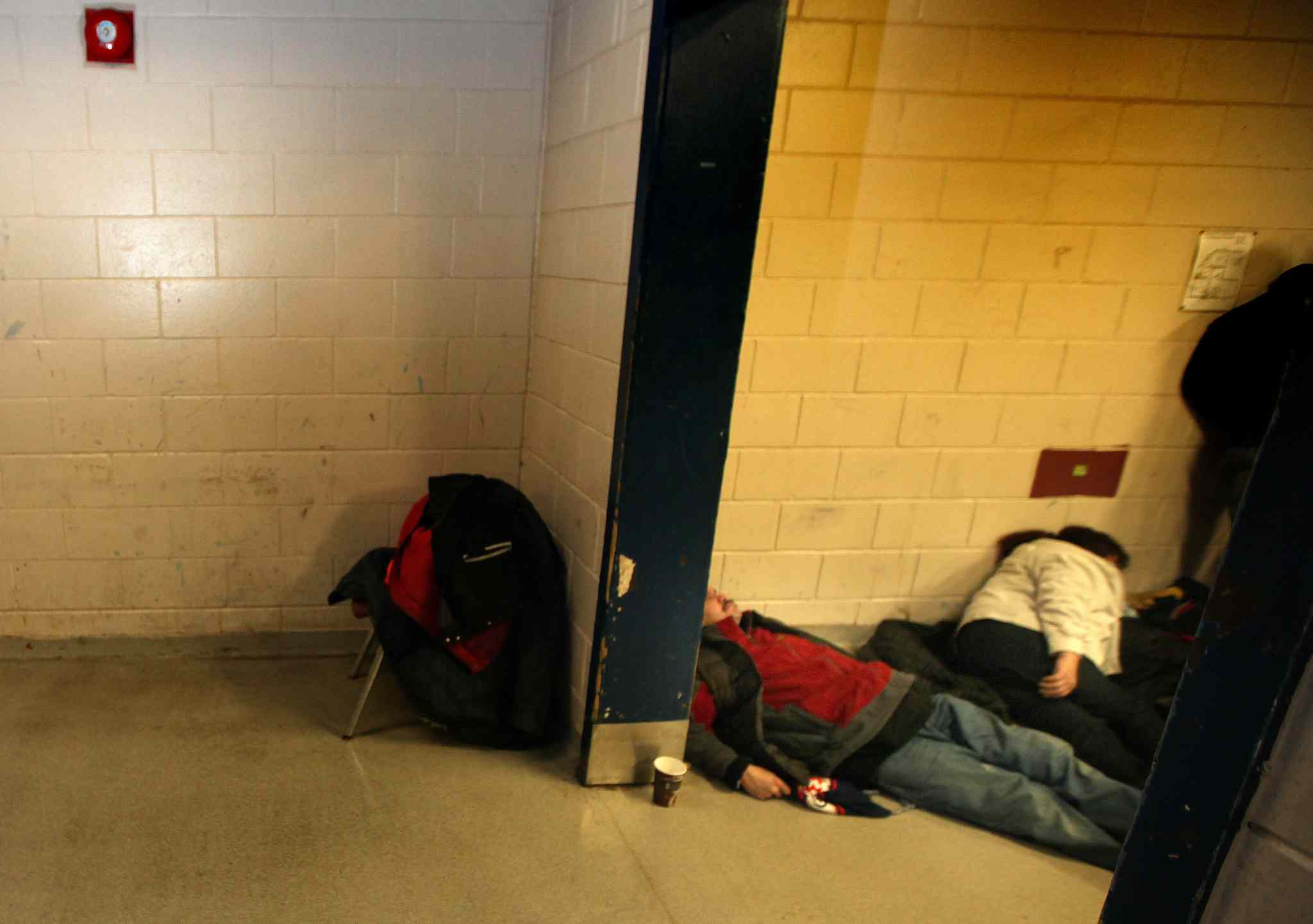 Clients wait in the Main Street Project for mats to be laid out on the floor to sleep on a cold January night in 2014.