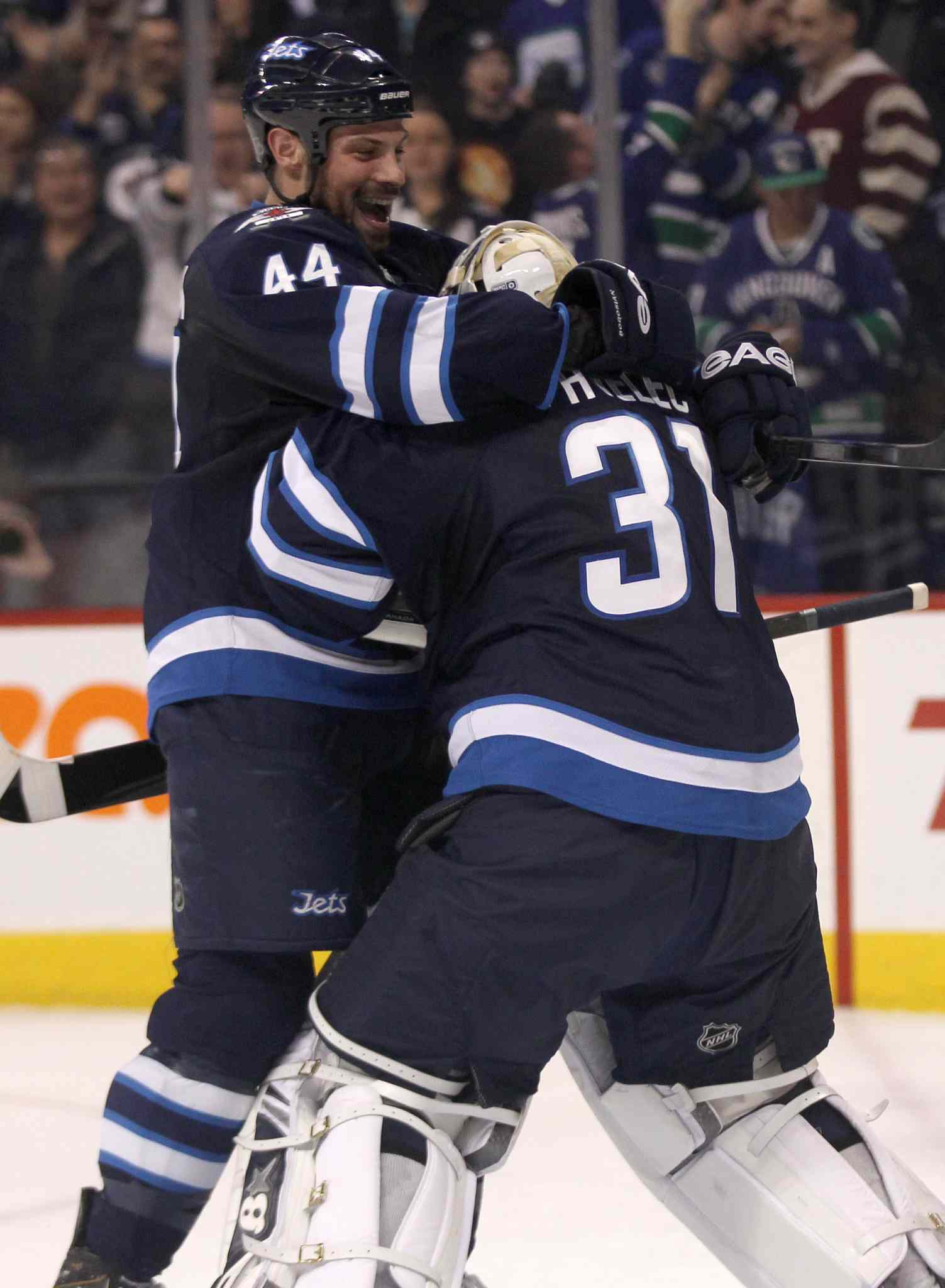 Winnipeg Jets' Zach Bogosian celebrates win over the Vancouver Canucks with goaltender Ondrej Pavelec after the Jets beat the Canucks 4-3 Friday night.