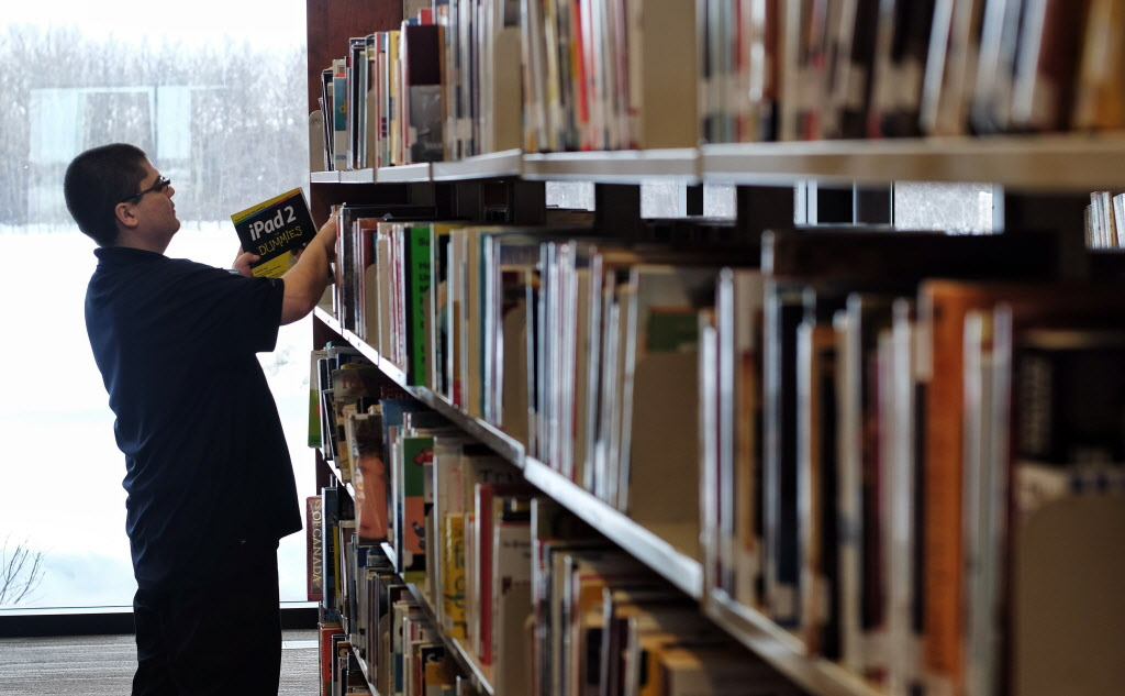 Library clerk, Brian Mercer, restocks the shelves at the recently opened Gaynor Family Regional Library in Selkirk, Manitoba, with a $1.5 m donation from the Gaynor family.  MIKE DEAL / WINNIPEG FREE PRESS