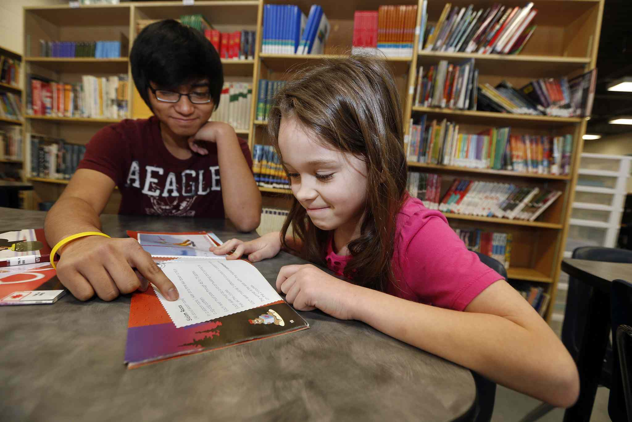 Grade 9 student Harvey Cabarlo helps Grade 2 student Lillian Hutchinson with her reading skills as part of the Book Buddies program at Sargent Park School. The Healthy Buddies program follows the same principle, with older kids mentoring younger ones in personal health.
