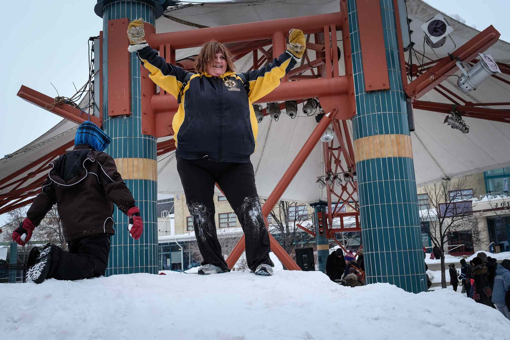 Tom jokingly bet Cathy she couldn't climb the large pile of snow by the skating rink at The Forks.