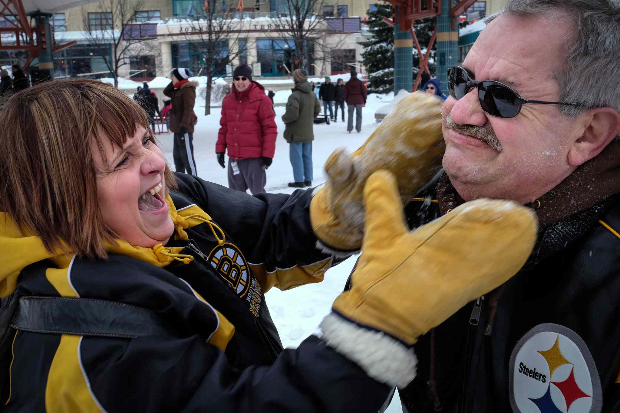 Cathy gives Tom a face full of snow after she slid down the hill of snow at The Forks.