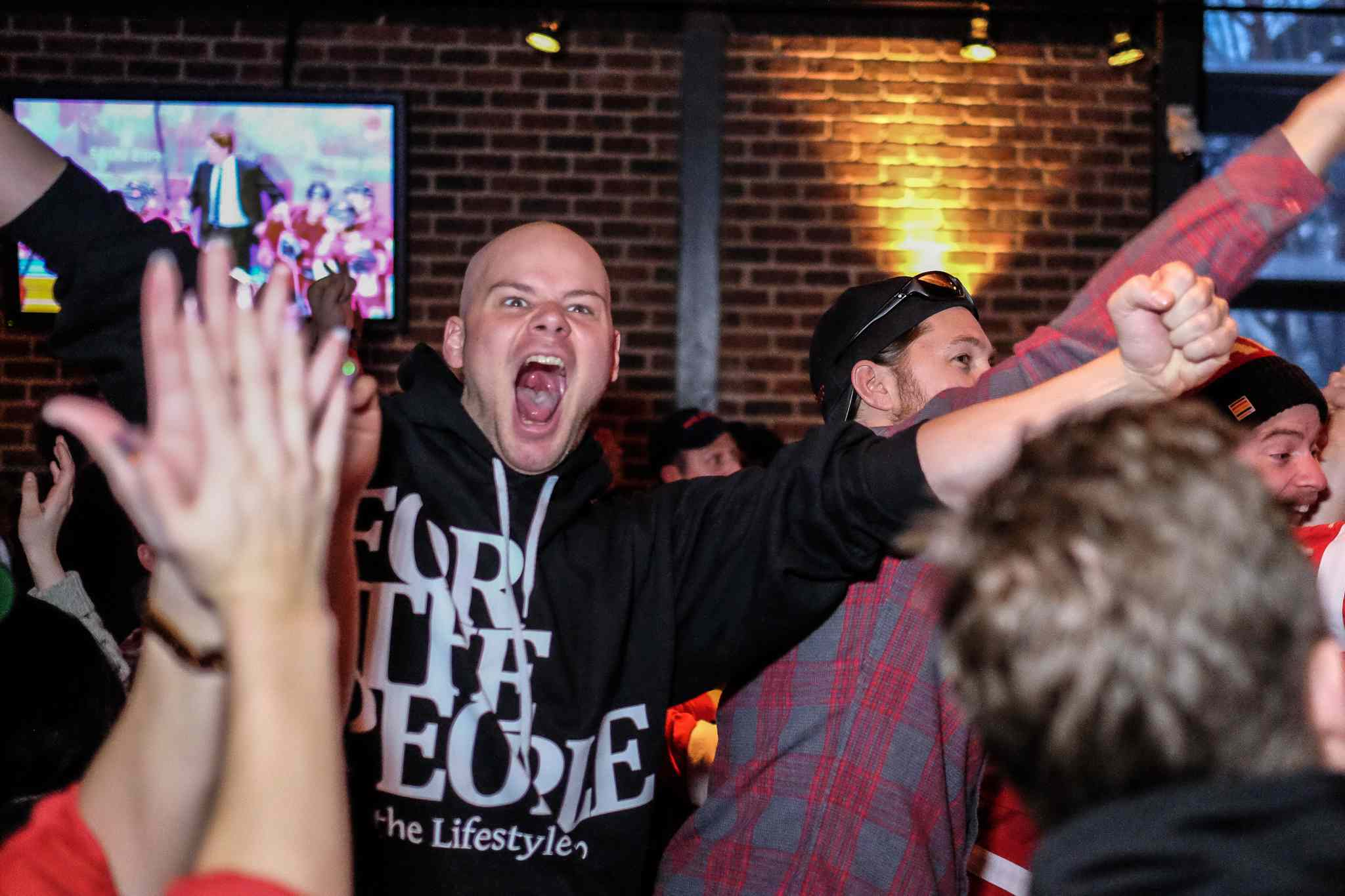 Jordan Lombaert cheers at Confusion Corner Bar & Grill after Team Canada scores its second goal during the men's hockey gold-medal game against Sweden at the Winter Olympics Sunday morning.