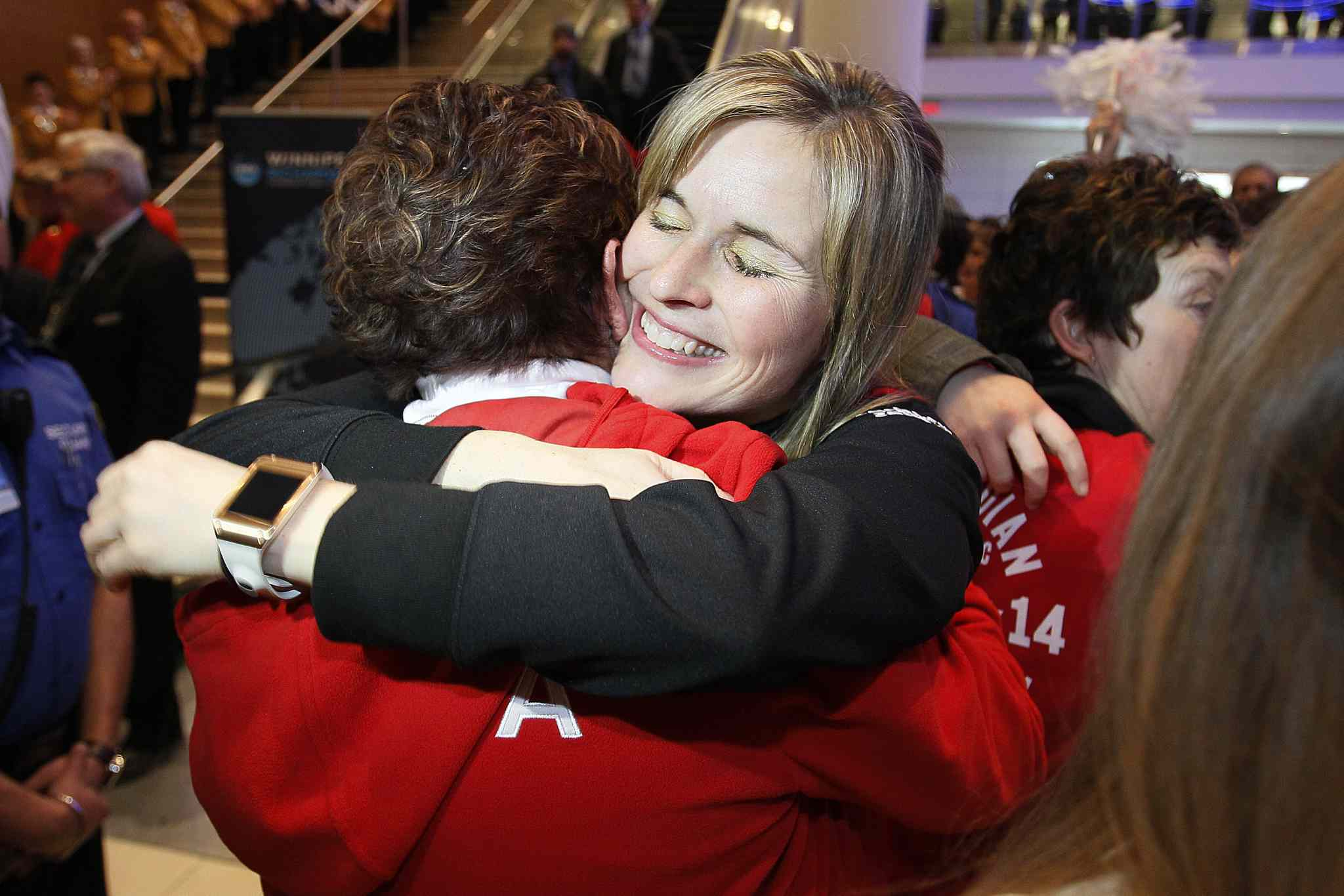 Hugs all around for Jones and her teammates as they arrive back in Winnipeg.