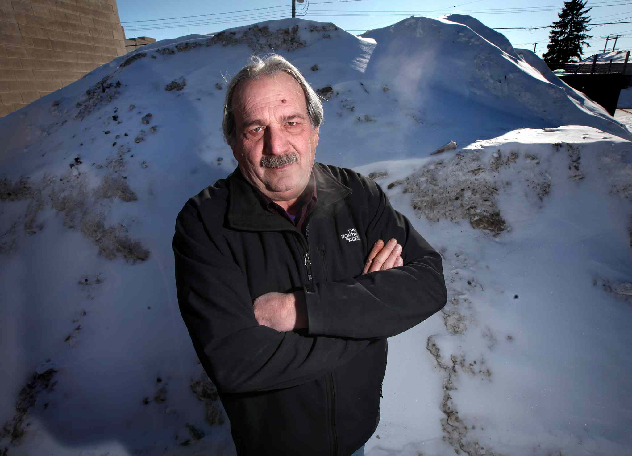Gino Riccio poses in front of the evidence: he caught city snow clearing crews dumping snow in his parking lot and has them on surveillance tape.