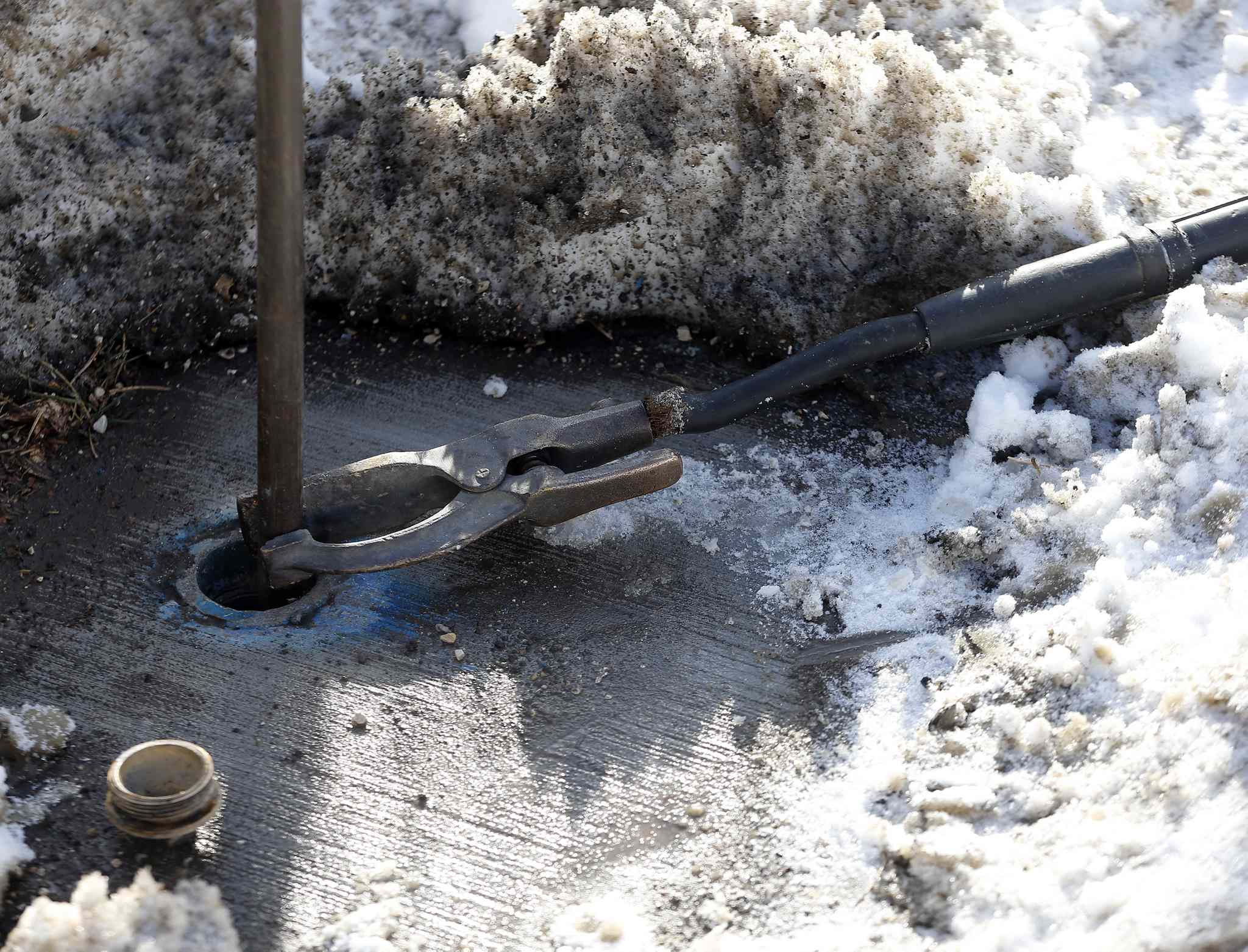 A city worker connects an electrical cable to heat a frozen water pipe.