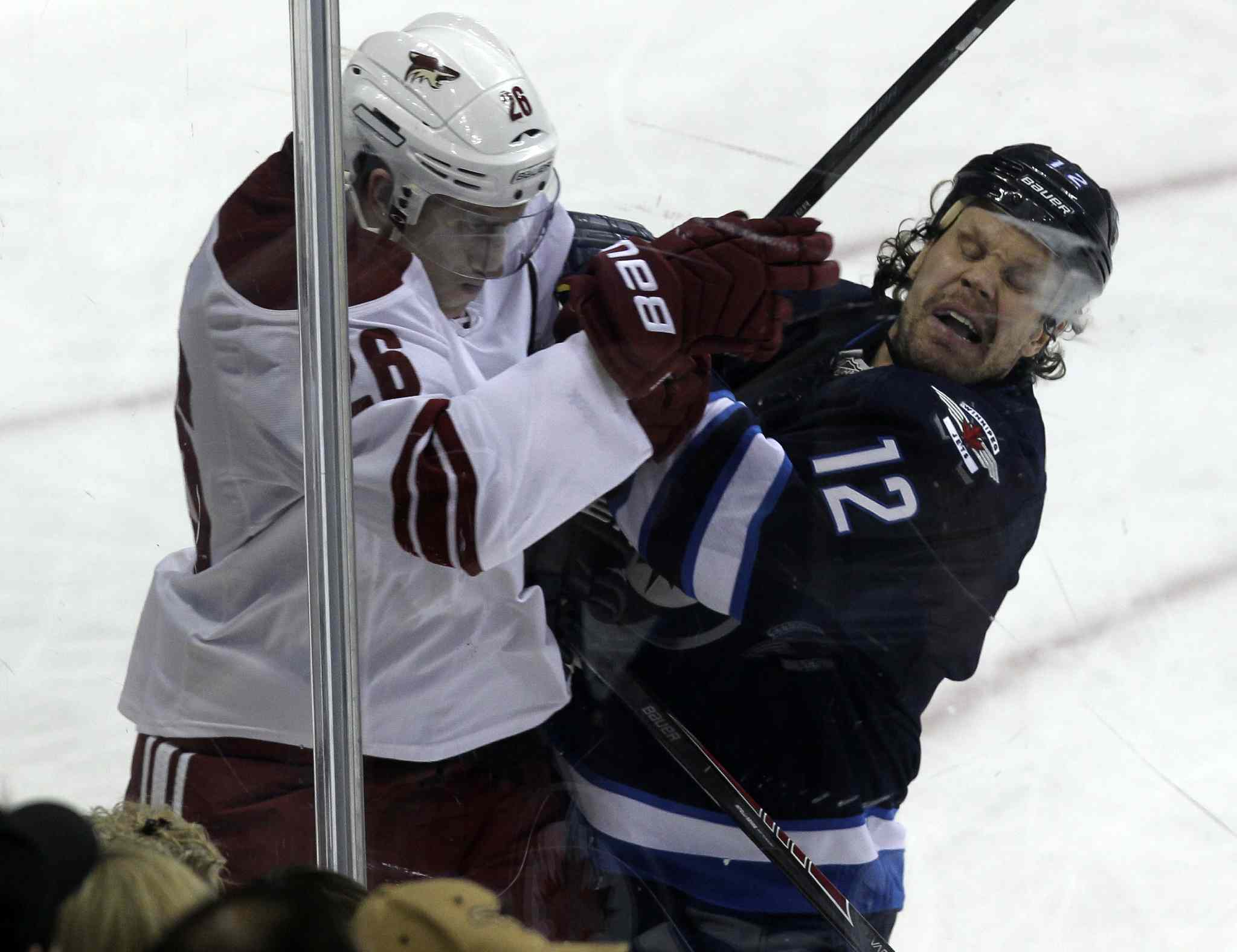 Winnipeg Jets' Olli Jokinen (12) slams Phoenix Coyotes' Michael Stone (26) into the boards during the first period of Thursday's game.
