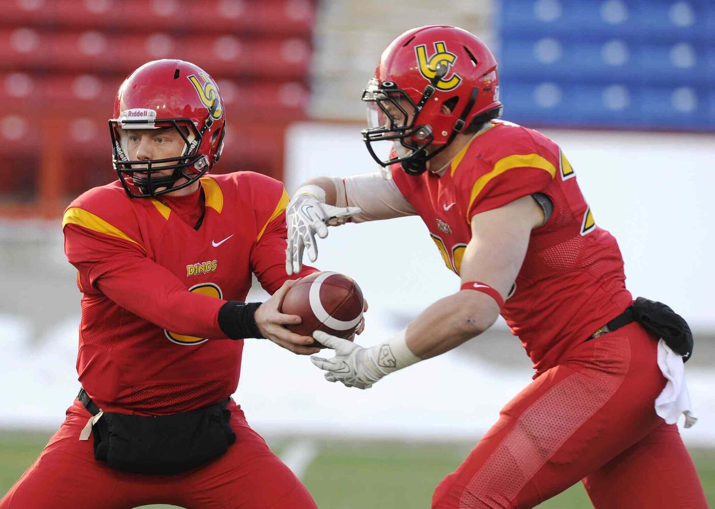 Dinos quarterback Andrew Buckley (left) hands off to Mercer Timmis during the first half.