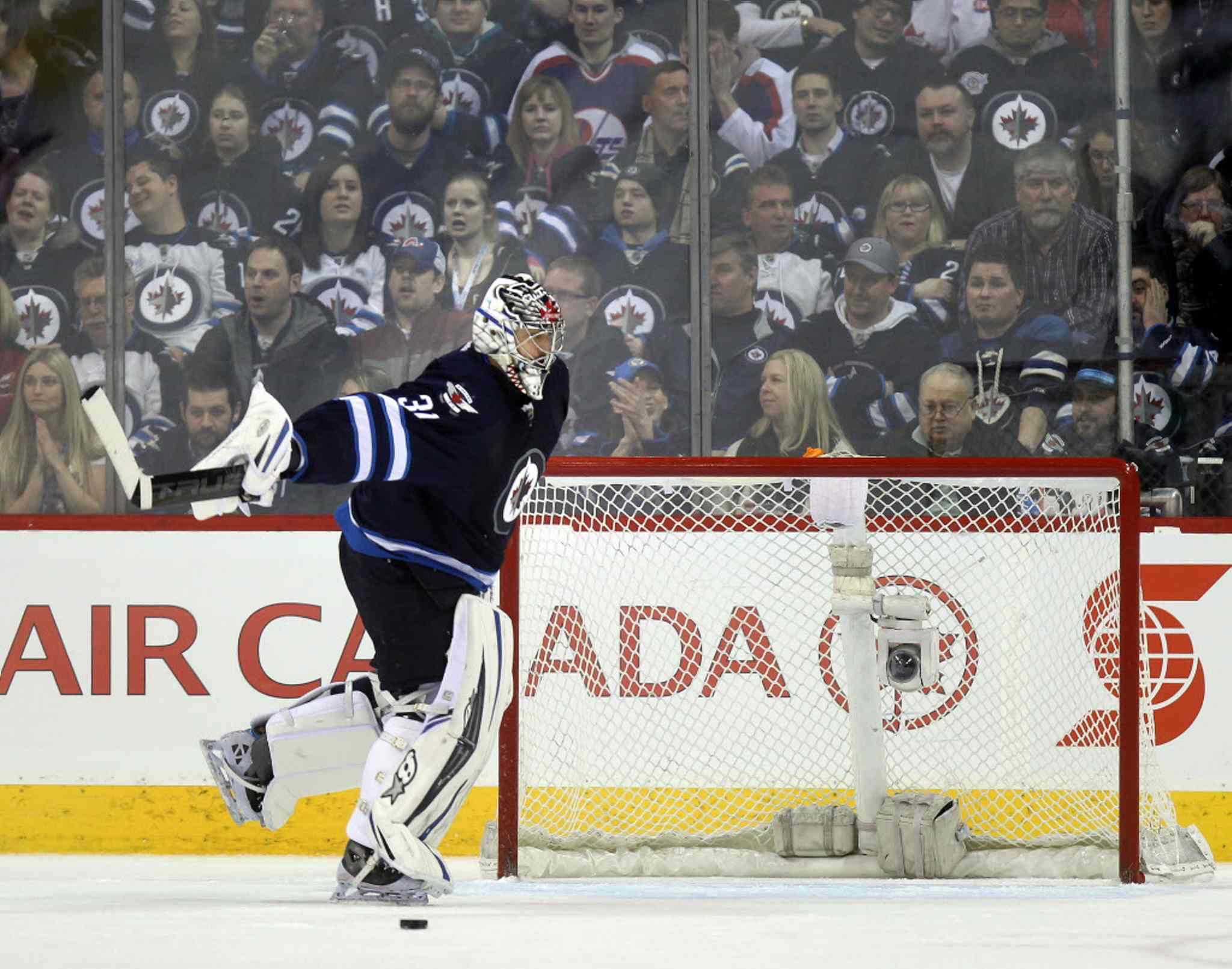 Ondrej Pavelec sweeps a goal by Los Angeles Mike Richards out of his net during the second period.