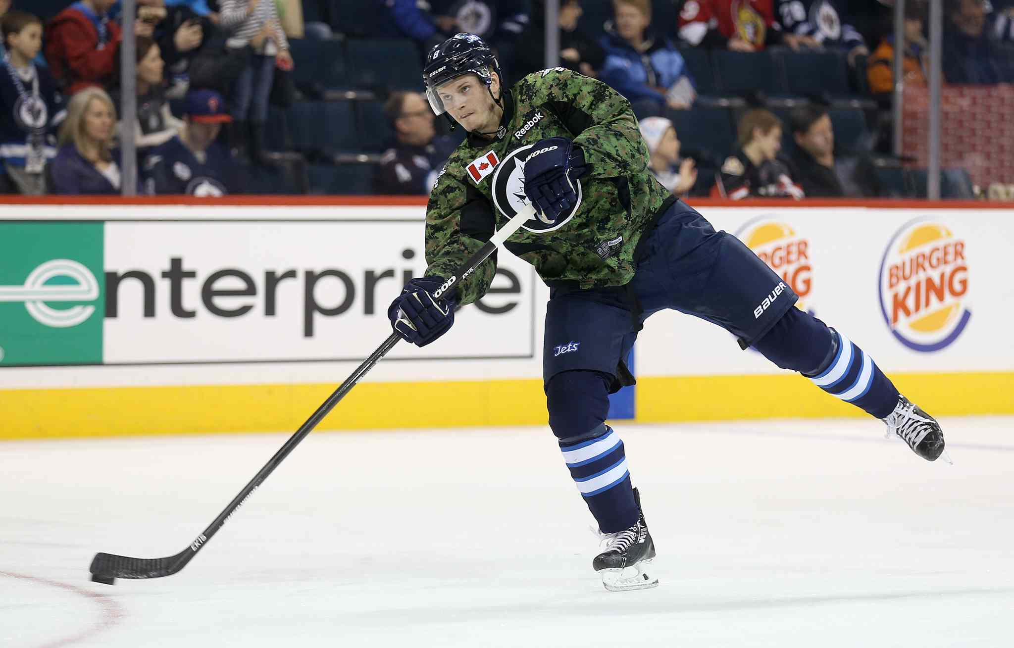 Winnipeg Jets' Jacob Trouba (8) fires a shot during warmup while wearing a camouflage jersey on Military Appreciation day prior to the game against the Ottawa Senators', Saturday, March 8, 2014.