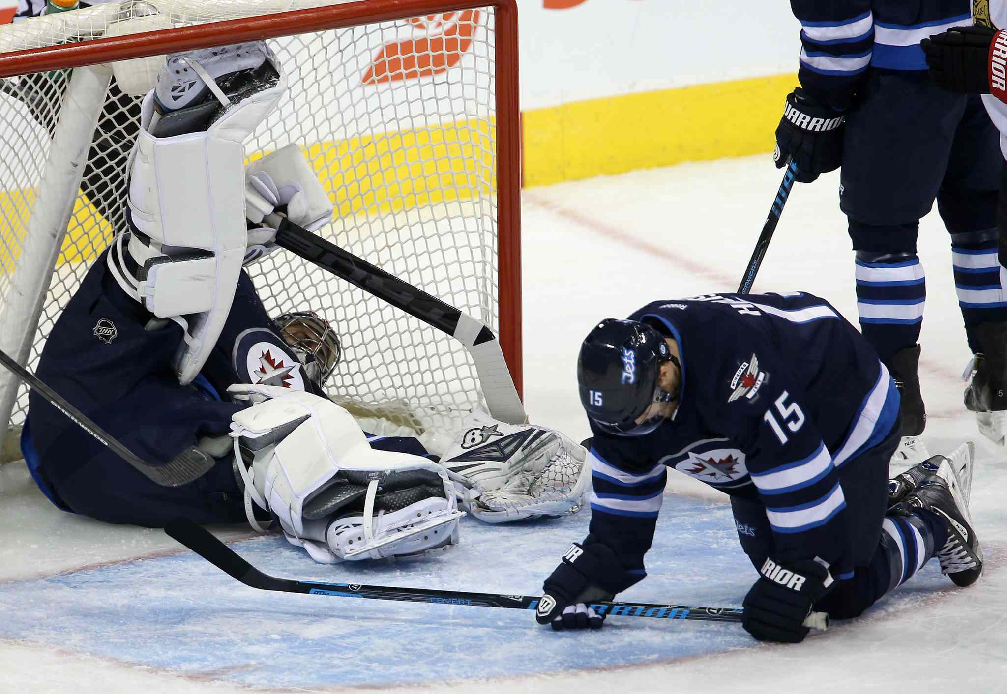 Winnipeg Jets' goaltender Ondrej Pavelec (31) lies in the net after a puck took a strange bounce off of Matt Halischuk (15). The goal was credited to Ottawa Senators' Milan Michalek (9), not shown, during first period NHL hockey action at MTS Centre in Winnipeg Saturday.