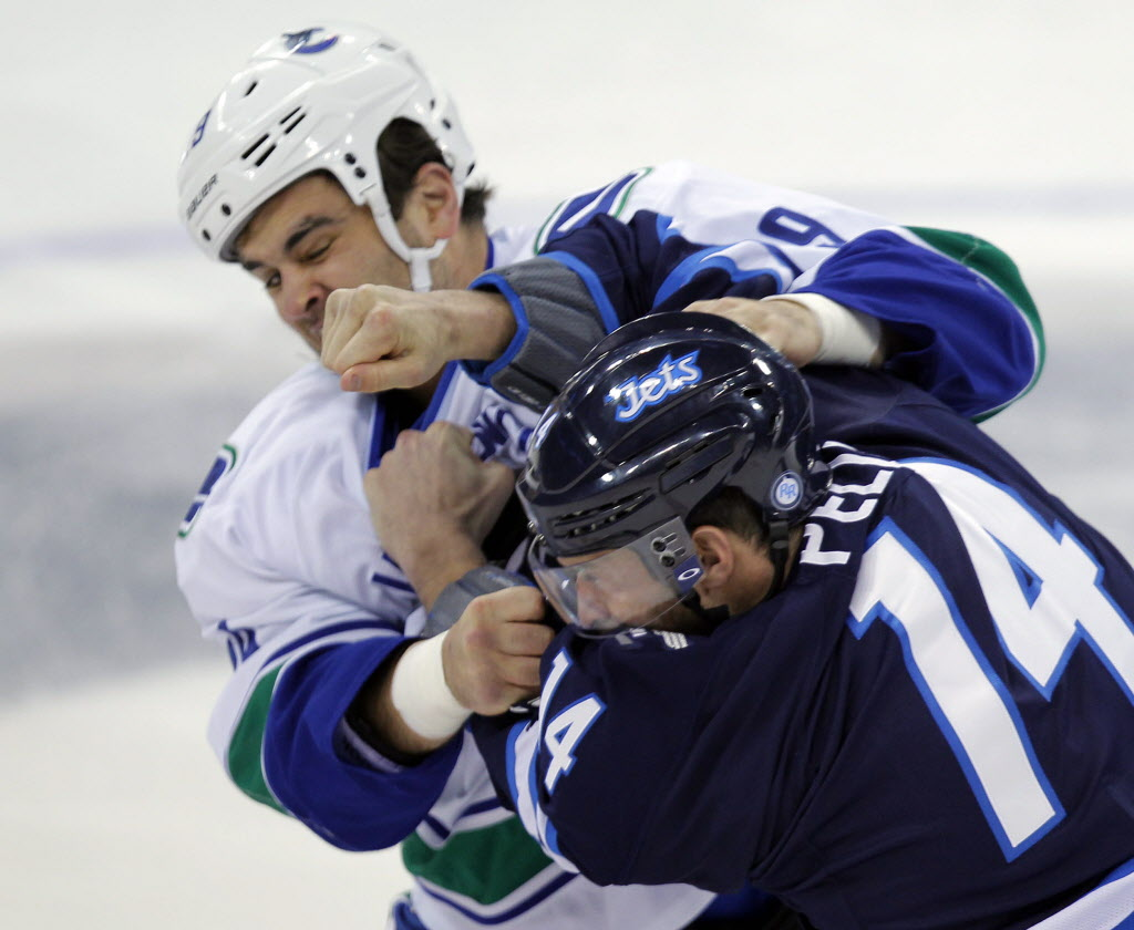 Jets' Anthoney Peluso (14) fights Canucks' Tom Sestito (29).
