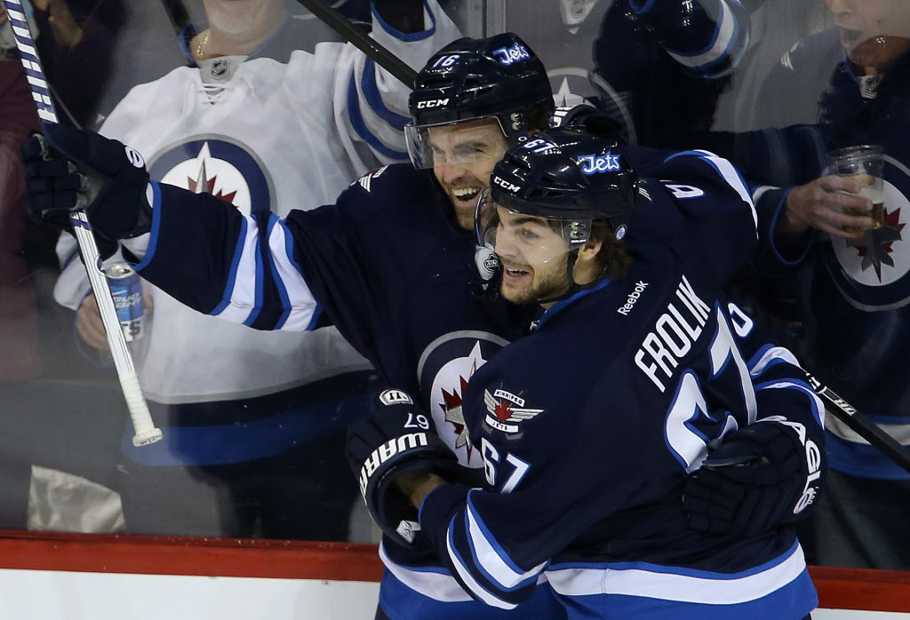 Winnipeg Jets' Andrew Ladd (16) and Michael Frolik (67) celebrate after Ladd scored on New York Rangers' goaltender Henrik Lundqvist (30) during the first period.