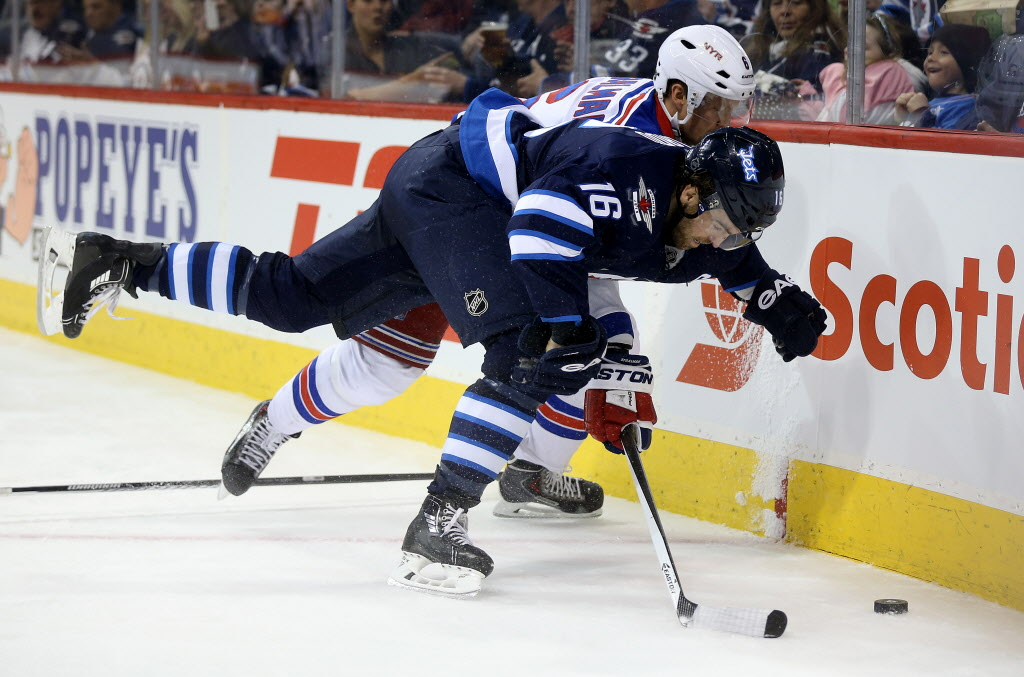 Winnipeg Jets' Andrew Ladd (16) and New York Rangers' Anton Stralman (6) battle during second period NHL hockey action at MTS Centre in Winnipeg.