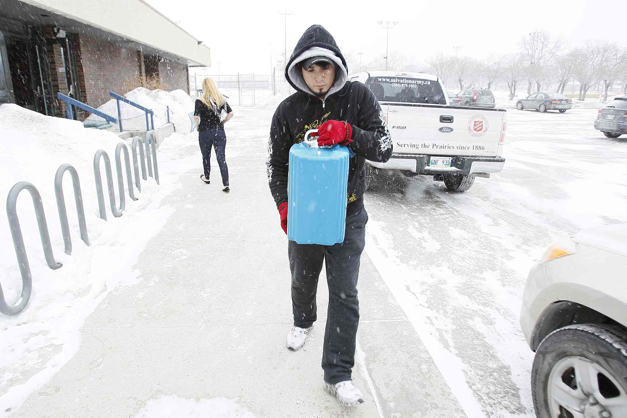 Marcelino Robles collects water for his family at the Cindy Klassen Rec Centre Sunday. His home's pipes have been frozen for a week.