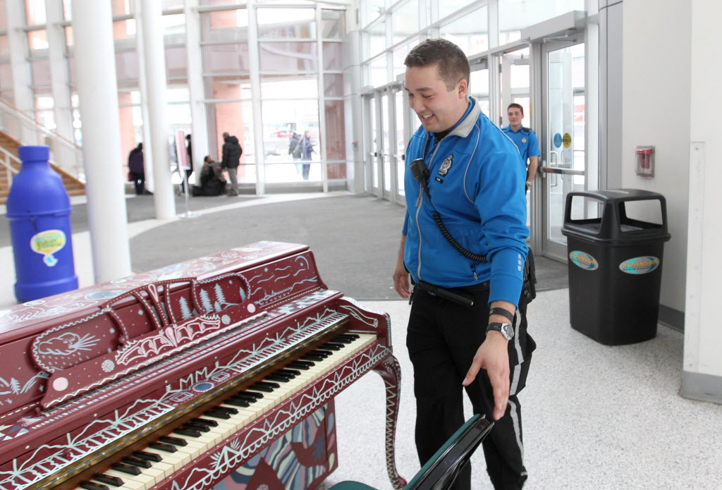 Police cadet Rob Klym sits down to try out a piano in the foyer at the MTS Centre Tuesday afternoon. (Ruth Bonneville / Winnipeg Free Press)