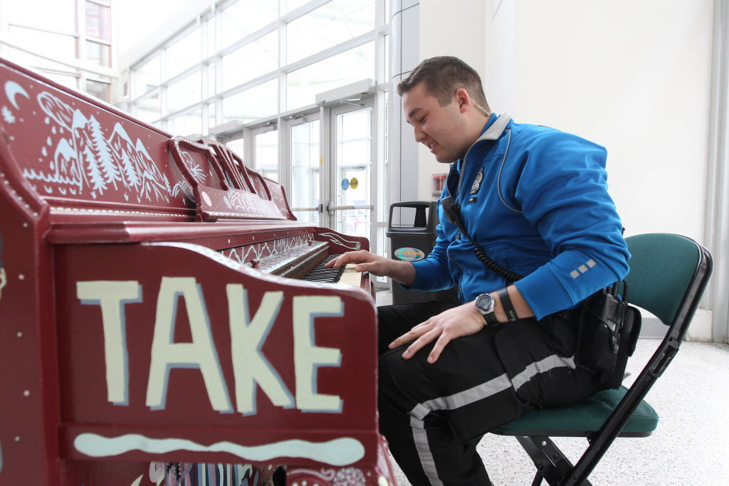 Police cadet Rob Klym sits down to tickle the ivories in the MTS centre foyer Tuesday afternoon. (Ruth Bonneville / Winnipeg Free Press)