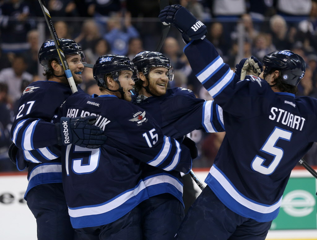 Winnipeg Jets' Eric Tangradi (27), Matt Halischuk (15), Jim Slater (19) and Mark Stuart (5) celebrate after Slater scored against the Carolina Hurricanes' during second period NHL hockey action. (TREVOR HAGAN / WINNIPEG FREE PRESS)