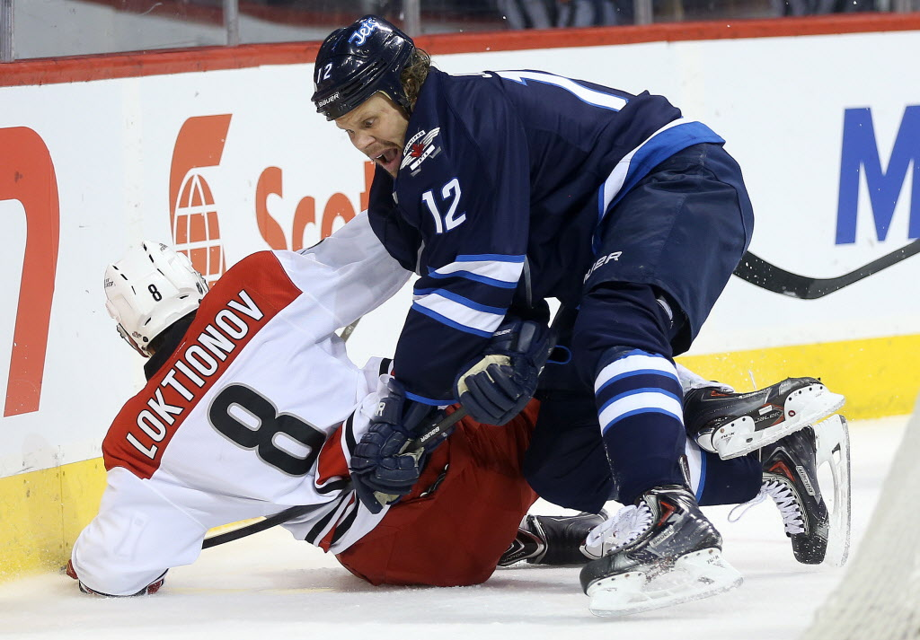 Winnipeg Jets' Olli Jokinen (12) hits Carolina Hurricanes' Andrei Loktionov (8) during second period NHL hockey action.  (TREVOR HAGAN / WINNIPEG FREE PRESS)