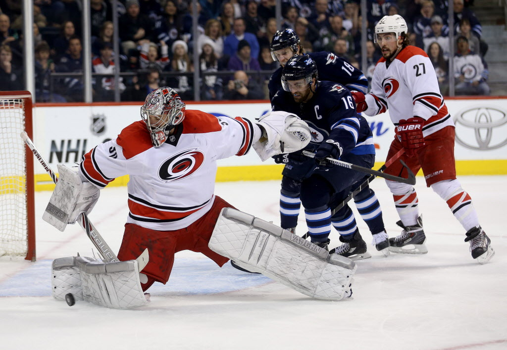 Carolina Hurricanes' goaltender Cam Ward (30) makes a save with Winnipeg Jets' Andrew Ladd (16) and Bryan Little (18) and Hurricanes' Justin Falk (27) in front of the net.