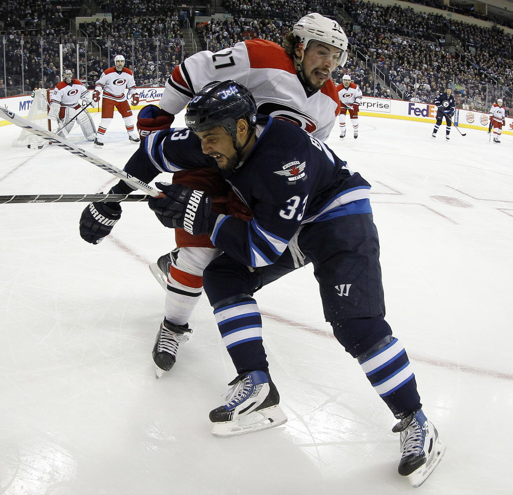 Winnipeg Jets' Dustin Byfuglien (33) hits Carolina Hurricanes' Justin Falk (27) during the second period.