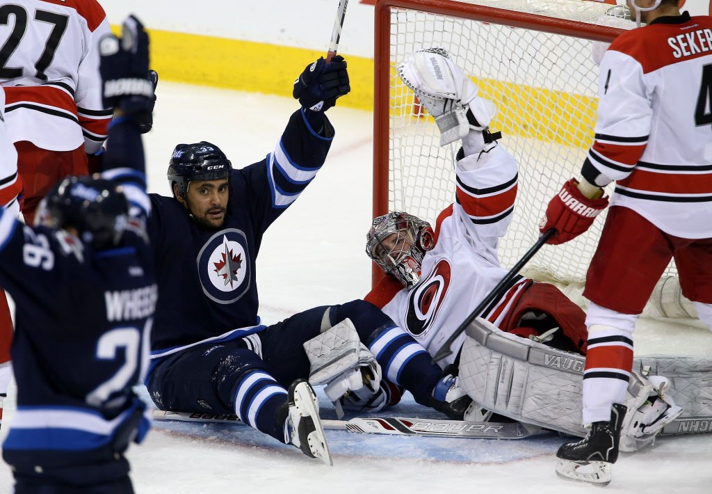 Winnipeg Jets' Dustin Byfuglien (33) celebrates and Carolina Hurricanes' goaltender Cam Ward (30) protests after a goal that would be disallowed during third period NHL hockey action.