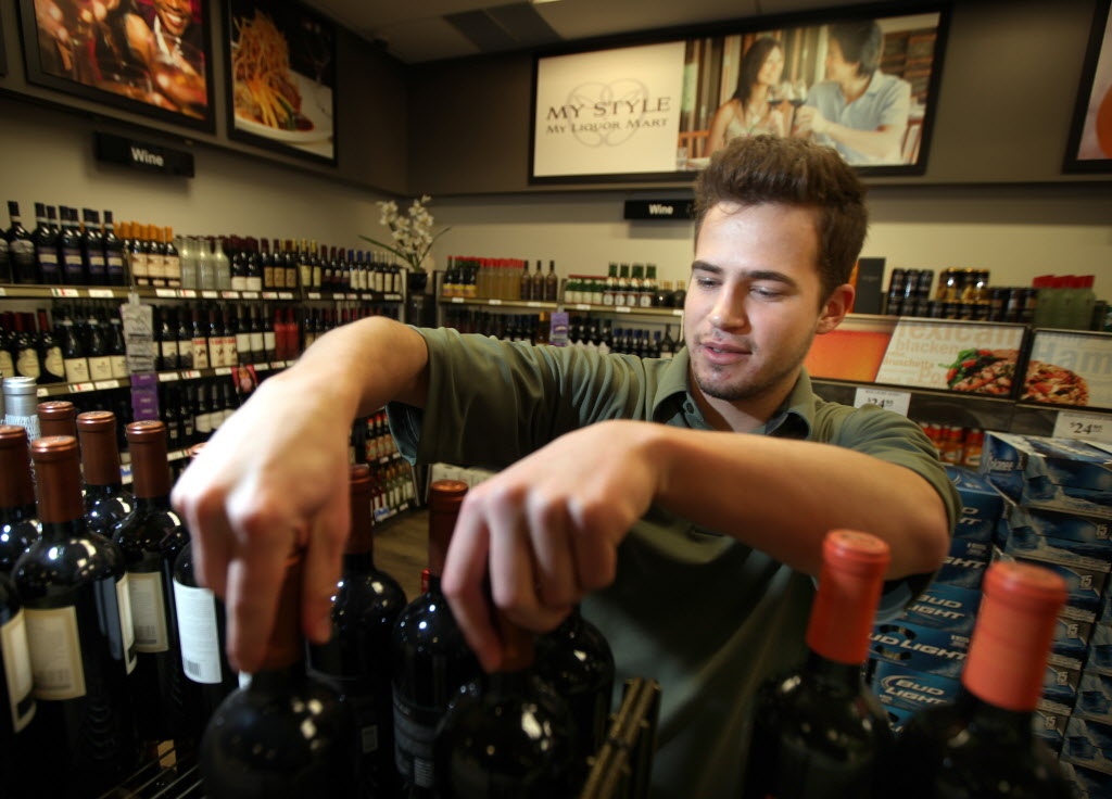 Daniel Van De Spiegle straightens a wine display at the Pembina Express mini liquor mart in the Pembina Village Safeway. Manitoba's liquor mini-mart experiment isn't going as planned.