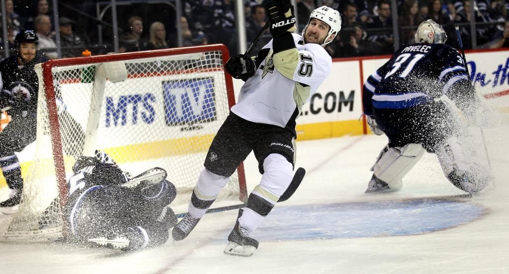 Winnipeg Jet Matt Halischuk dissappears into a dislodged net after a hit from Pittsburgh Penquin Tanner Glass (15) Thursday at the MTS Center in first period action.  (Phil Hossack / Winnipeg Free Press)