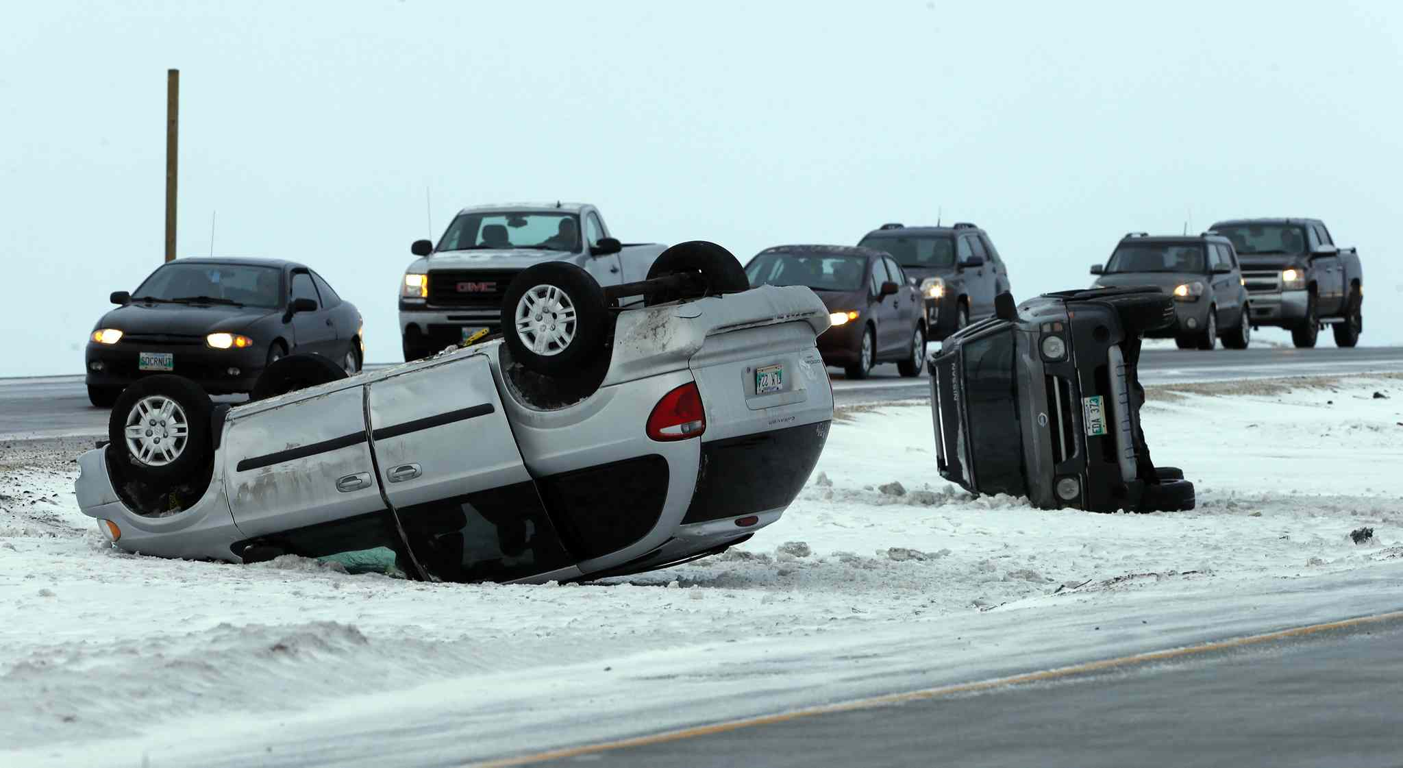 Two cars are seen flipped over and off the road due to glare ice conditions east of Centreport Canada Way.