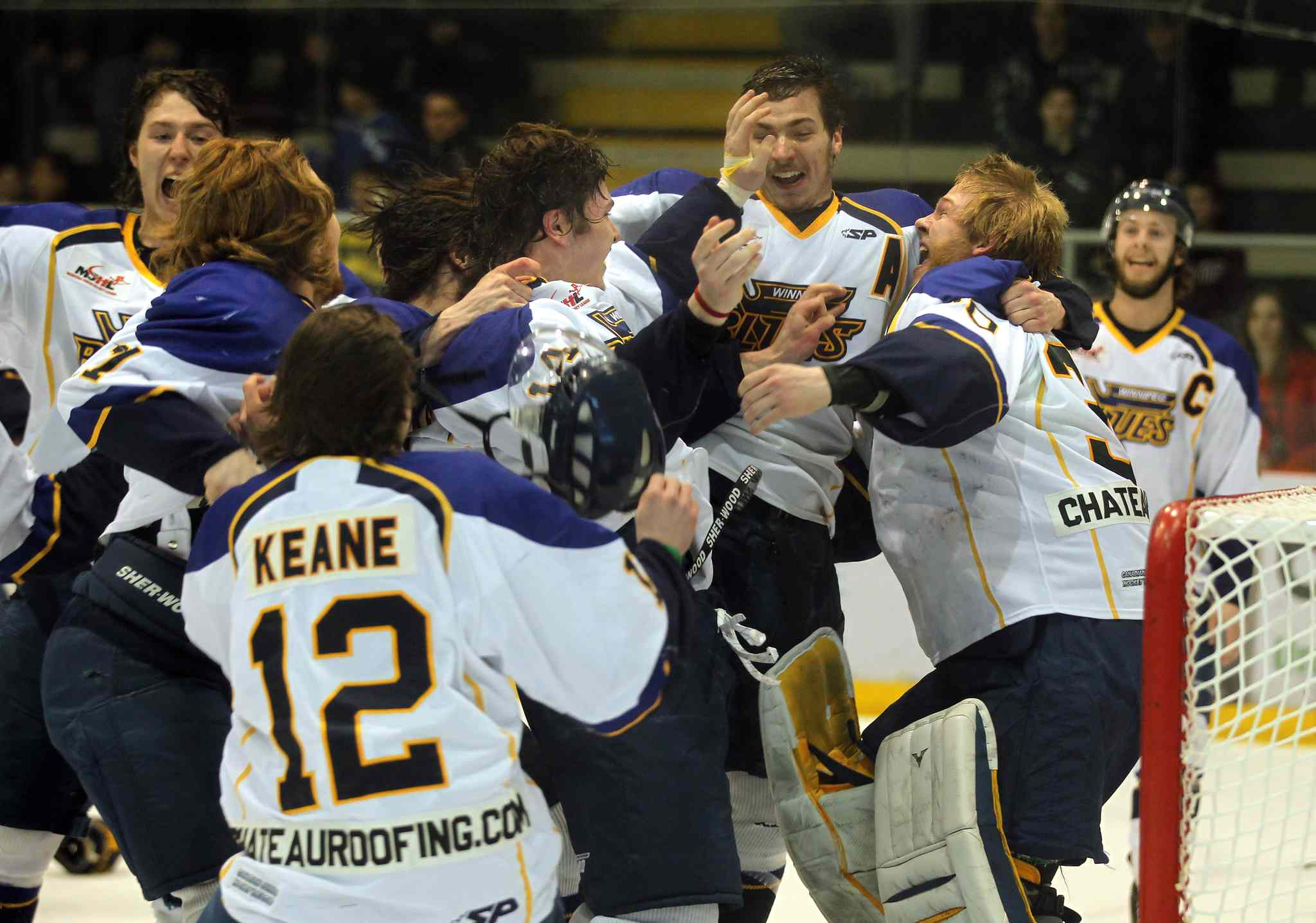 Elated Winnipeg Blues players celebrate with goalie Byron Spriggs (right) after the team defeated the Dauphin Kings 5-1 at the MTS Iceplex Tuesday.