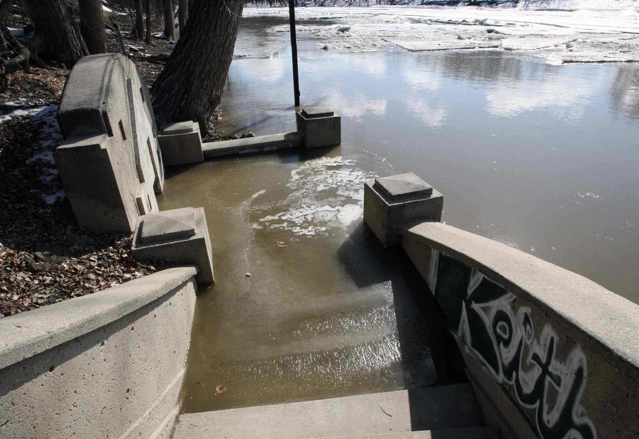The Assiniboine River rises above the riverwalk and stairs near the Manitoba Legislature Monday.