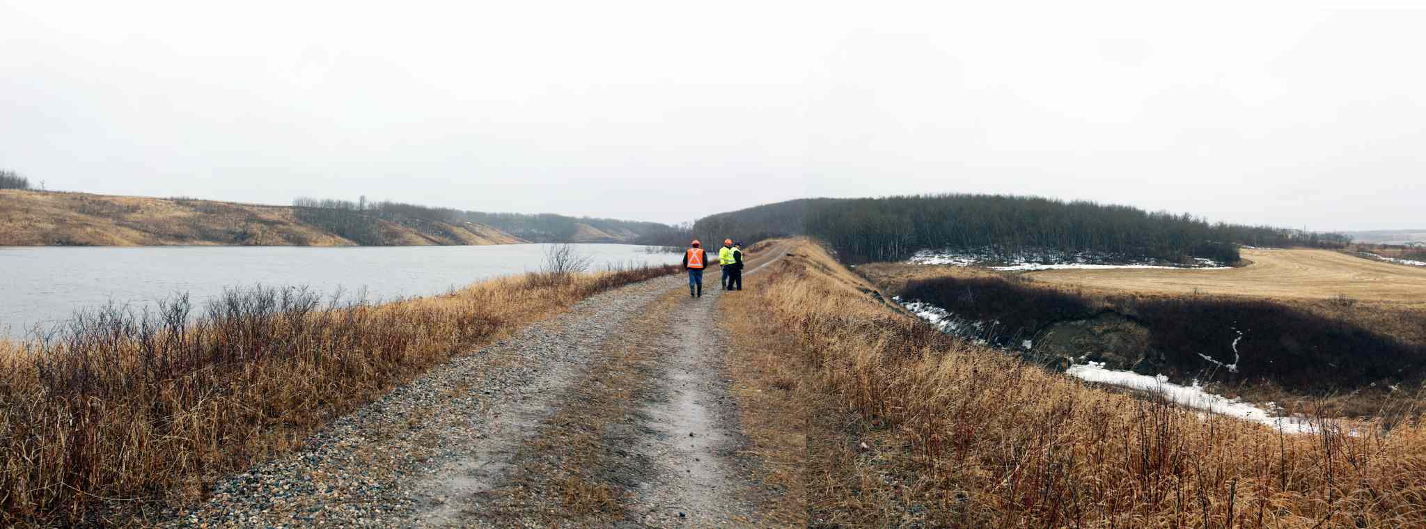 In this composite image created from two separate images, MIT officials walk along the embankment on a tributary to Birdtail Creek in Waywayseecappo First Nation where frozen culverts have caused water to build up above the community on Monday afternoon.
