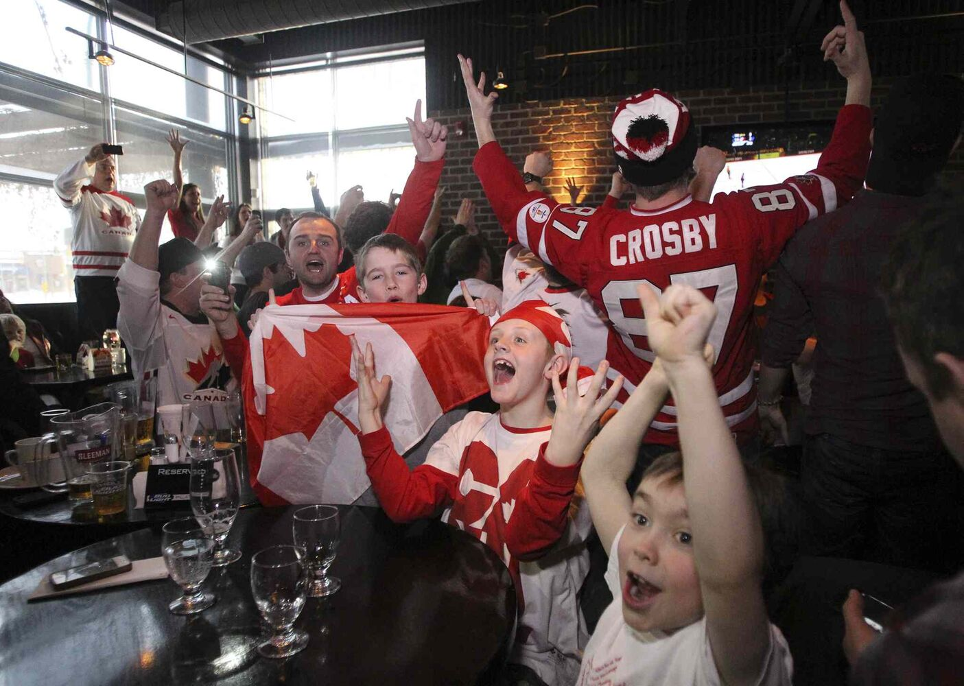 Little fans Jackson Zuk (holding flag), 8, Jack Derrett (centre), 9, and Grey Davidson (right), 7, are thrilled after Canada wins the gold medal.