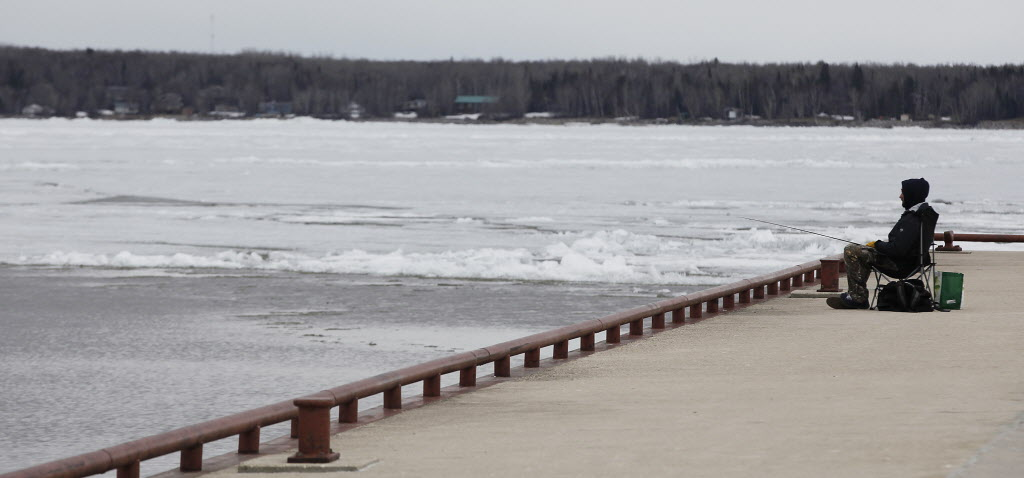 Kyle Otter tries his luck by throwing his line in a thawed section of Lake Winnipeg.  (John Woods / Winnipeg Free Press)