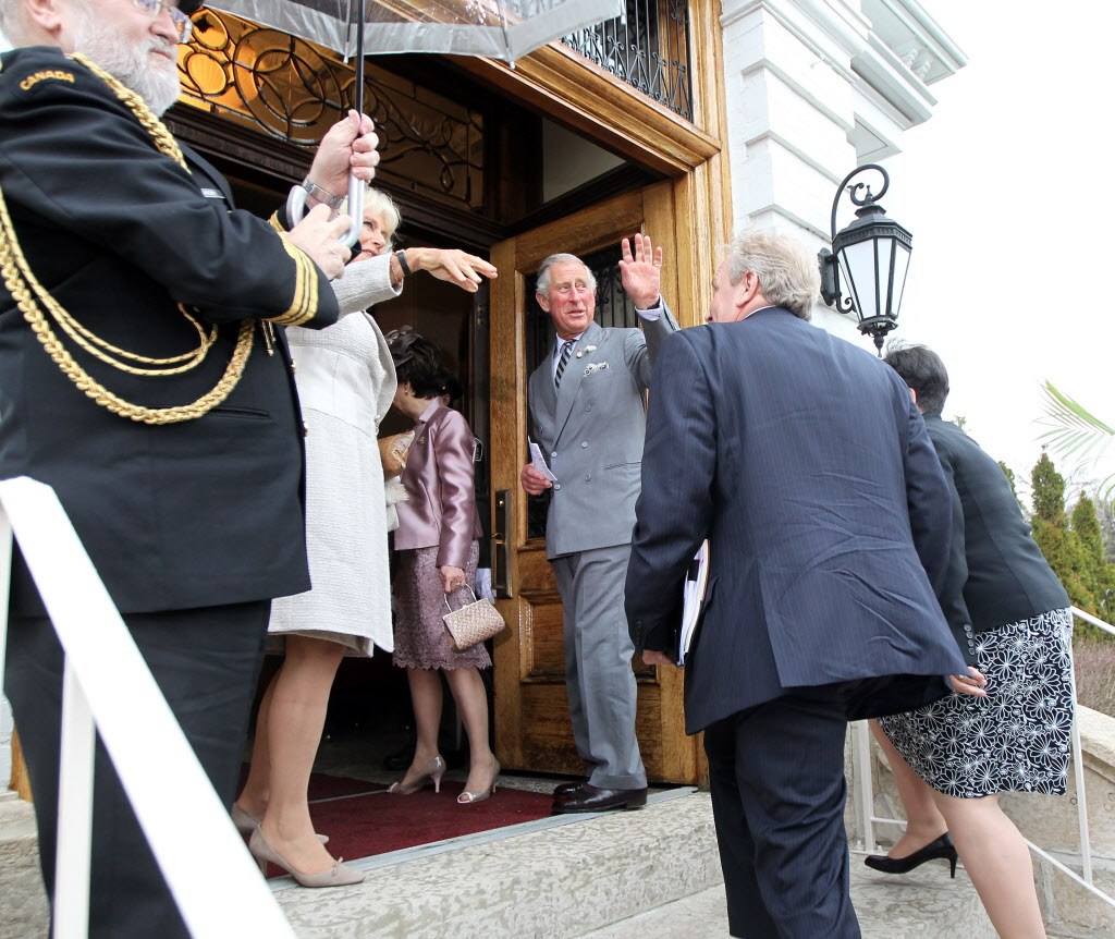 Their Royal Highnesses The Prince of Wales and The Duchess of Cornwall wave to spectators outside Government House.