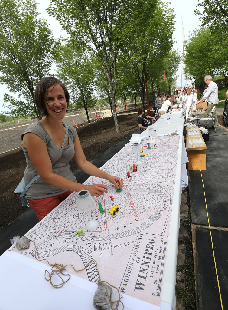 Jane Stewart prepares her and her friends' table for Table for 1200, on the Esplanade Riel Bridge on Saturday. (Jason Halstead / Winnipeg Free Press)