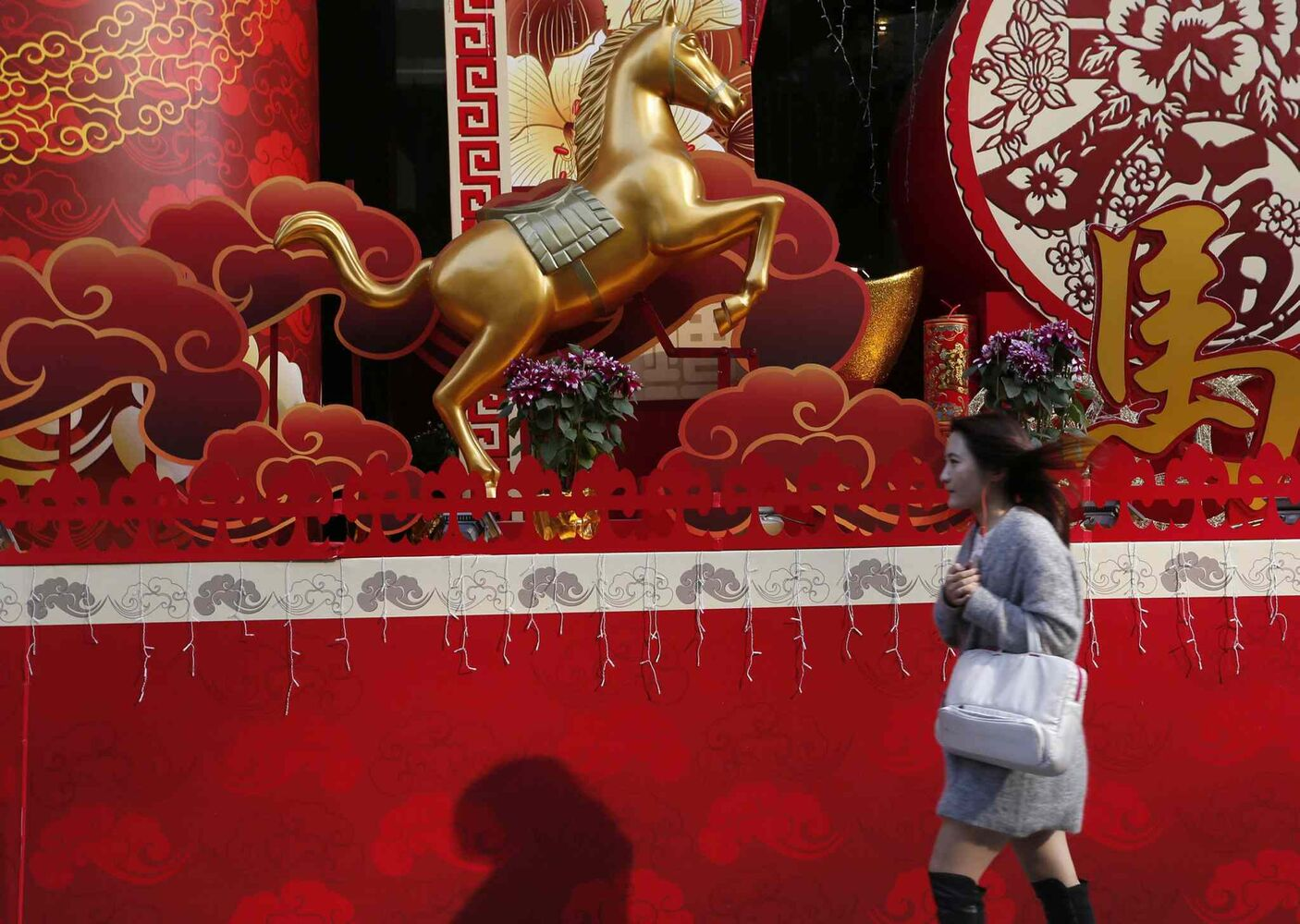 In this Monday, Jan. 27, 2014 photo, Chinese New Year decorations with a golden horse are displayed outside a building in Hong Kong. Hong Kong expected 7.93 million visitors for New Year celebrations, more than territory's permanent population of 7.1 million.
